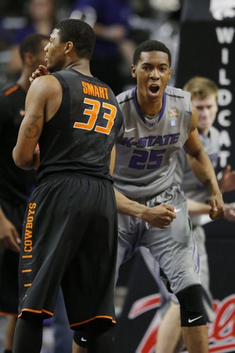 Kansas State forward Wesley Iwundu (25) and Oklahoma State guard Marcus Smart (33) at the end of an NCAA college basketball game at Bramlage Coliseum in Manhattan, Kan., Saturday, Jan. 4, 2014. Kansas State defeated Oklahoma State 71-74. (AP Photo/Orlin Wagner)