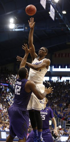 Kansas center Joel Embiid floats a shot high over Kansas State forward Thomas Gipson during the second half on Saturday, Jan. 11, 2014 at Allen Fieldhouse.
