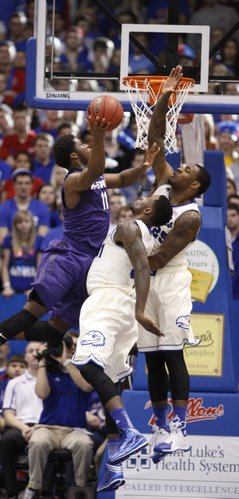 Kansas teammates Jamari Traylor, center, and Tarik Black defend against a shot by Kansas State forward Nino Williams during the second half on Saturday, Jan. 11, 2014 at Allen Fieldhouse.