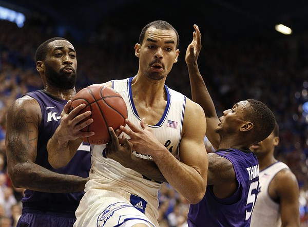 Kansas forward Perry Ellis comes down with a rebound between Kansas State players Thomas Gipson, left, and Jevon Thomas during the second half on Saturday, Jan. 11, 2014 at Allen Fieldhouse.