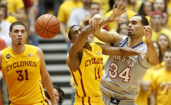 Kansas forward Perry Ellis battles for the ball with Iowa State guard Monte Morris during the first half on Monday, Jan. 13, 2014 at Hilton Coliseum in Ames, Iowa. At left is ISU forward Georges Niang.