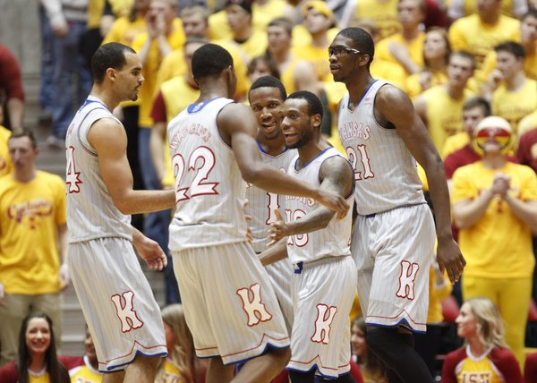 Kansas teammates celebrate a three-pointer by point guard Naadir Tharpe, center against Iowa State during the first half on Monday, Jan. 13, 2014 at Hilton Coliseum in Ames, Iowa.