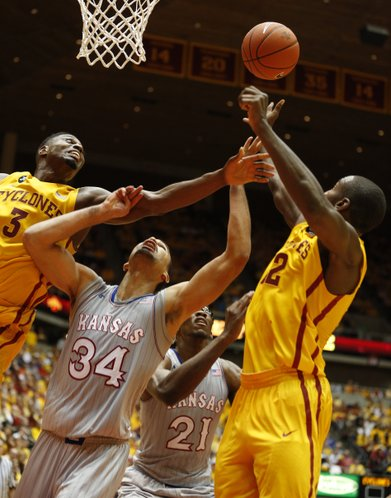 Kansas forward Perry Ellis looks for a rebound between Iowa State defenders Melvin Ejim, left, and Dustin Hogue during the second half on Monday, Jan. 13, 2014 at Hilton Coliseum in Ames, Iowa.