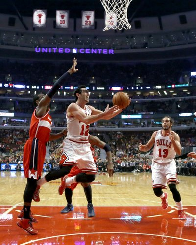 Chicago Bulls guard Kirk Hinrich (12) drives past Washington Wizards guard John Wall, left, as Joakim Noah (13) watches during the first half of an NBA basketball game Monday, Jan. 13, 2014, in Chicago. (AP Photo/Charles Rex Arbogast)