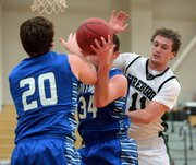 Free State's Blake Winslow (11) fights for the ball against Leavenworth players in the first half on Tuesday, Jan. 14, 2014, at FSHS. The Firebirds boys won, 69-55.