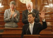 Gov. Sam Brownback delivers his annual State of the State address in the House of Representatives at the Statehouse in Topeka, Wednesday, Jan. 15, 2014. Brownback's speech outlined his policy priorities for the 2014 legislative session. Behind Brownback are Senate president Susan Wagle and Speaker of the House Ray Merrick.