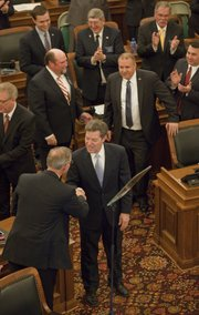Gov. Sam Brownback greets Rep. Paul Davis D-Lawrence, as Brownback enters the House of Representatives to deliver his State of the State address at the Statehouse in Topeka, Wednesday, Jan. 15, 2014.
