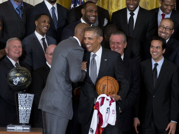 President Barack Obama holds a basketball and Miami Heat basketball jersey and shakes hands with Miami Heat player Ray Allen during a ceremony in the East Room of the White House in Washington,, Tuesday, Jan. 14, 2014, where the president honored the 2013 NBA Champion basketball team on their second-straight title. Behind them are Miami Heat forward LeBron James, team president Pat Riley is second from left, Miami Heat head coach Erik Spoelstra is at left. . (AP Photo/Carolyn Kaster)