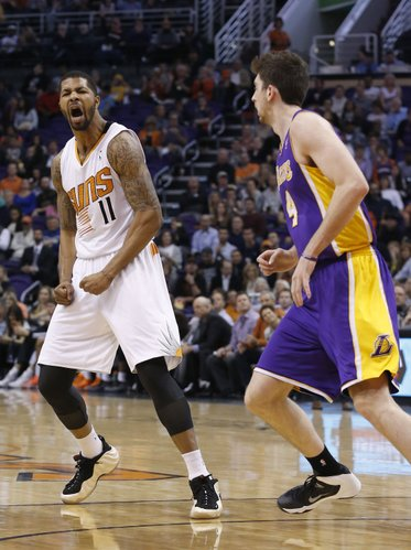 Phoenix Suns' Markieff Morris (11) shouts in celebration after scoring over Los Angeles Lakers' Ryan Kelly (4) during the second half of an NBA basketball game Wednesday, Jan. 15, 2014, in Phoenix. The Suns defeated the Lakers 121-114. (AP Photo/Ross D. Franklin)