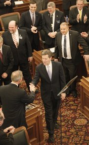 Gov. Sam Brownback greets Rep. Paul Davis D-Lawrence, as Brownback enters the Kansas House of Representatives chamber to deliver his State of the State address at the Statehouse, Wednesday, Jan. 15, 2014. I planned out my photo position and angle of coverage, in advance to better predict a story-telling photograph.