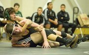 Topeka High's Michael Malleck, front, is unable to escape the grasp of Free State sophomore Kelvin Suddith during their 145# wresting match, Thursday evening at FSHS.