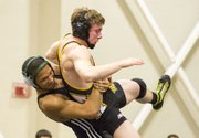 Free State freshman Tyreik Gooch, left, throws Topeka High's Daniel Stous to the mat during their 152# wresting match, Thursday evening at FSHS.