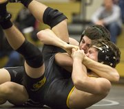 Free State sophomore Sid Miller, back, hooks the leg of Topeka High's Johnny Thomas as he works for a pin during their 120# wresting match, Thursday evening at FSHS.