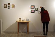 A patron looks at some of the tiny works of art on display at the Itty Bitty Picture Show, featuring art no larger than 4-by-6 inches, at the Lumberyard Arts Center in Baldwin City on Thursday. The exhibit features 56 works by 16 area artists.