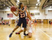 Lawrence High senior Kionna Coleman tries to slow down Olathe East's Whitney Nelson (23) during their game Friday evening at LHS.