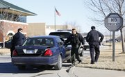 Law enforcement officials gather into their vehicles outside the Prosoco building, 3741 Greenway Circle, at the East Hills Business Park on Friday, Jan. 17, 2014.  Law enforcement officials spent nearly two hours searching for a suspect who was reportedly armed and distraught.