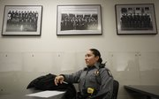 Patrol officer Ashley Durazo, 24, sits below portraits of police officers from years past during a recent shift briefing at the Douglas County Judicial and Law Enforcement Center. Durazo has been with the Lawrence Police Department for a little more than two years and is among the youngest of the department's officers.