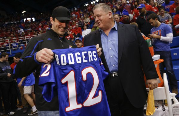 Green Bay Packers quarterback Aaron Rodgers receives a Kansas football jersey from head coach Charlie Weis prior to Saturday's basketball game against Oklahoma State at Allen Fieldhouse.