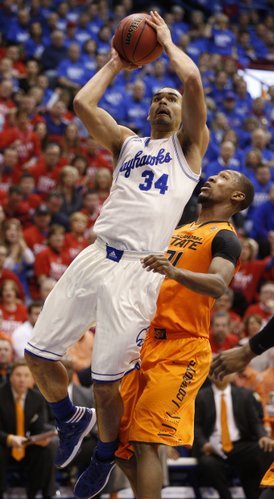 Kansas forward Perry Ellis floats in for a bucket past Oklahoma State forward Kamari Murphy during the first half on Saturday, Jan. 18, 2014 at Allen Fieldhouse.
