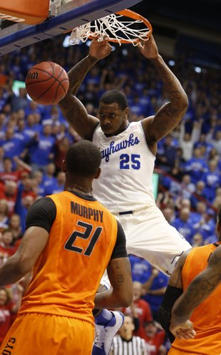 Kansas forward Tarik Black delivers on a dunk before Oklahoma State forward Kamari Murphy during the first half on Saturday, Jan. 18, 2014 at Allen Fieldhouse.