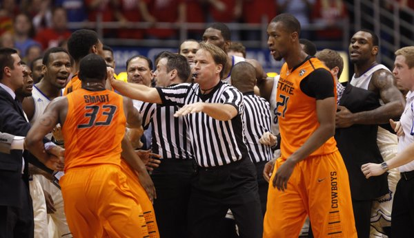 Game officials break up a skirmish between the Kansas and Oklahoma State players during the first half on Saturday, Jan. 18, 2014 at Allen Fieldhouse.