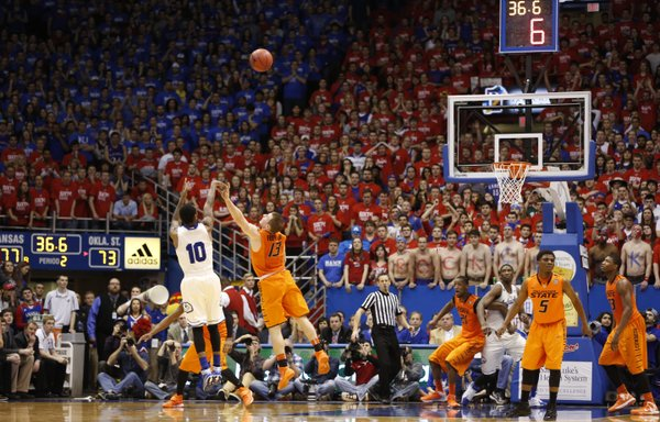Kansas guard Naadir Tharpe puts up a three over Oklahoma State guard Phil Forte with seconds remaining in the second half on Saturday, Jan. 18, 2014 at Allen Fieldhouse. Tharpe hit the three to widen the Jayhawks' lead.