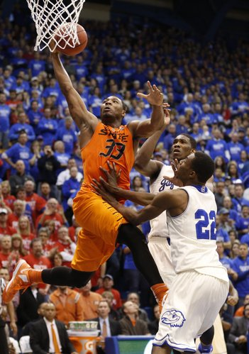 Oklahoma State guard Marcus Smart goes to the bucket against Kansas defenders Joel Embiid and Andrew Wiggins (22) late in the second half on Saturday, Jan. 18, 2014 at Allen Fieldhouse.