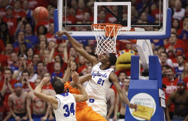 Kansas center Joel Embiid rejects a shot from Oklahoma State guard Markel Brown during the first half on Saturday, Jan. 18, 2014 at Allen Fieldhouse. Also pictured is Kansas forward Perry Ellis.