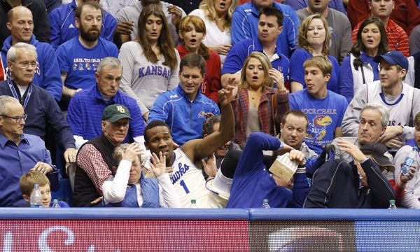 Fans react as Kansas guard Wayne Selden crashes into the seats after saving a ball that was tossed to teammate Joel Embiid for a bucket during the second half on Monday, Jan. 20, 2014 at Allen Fieldhouse.