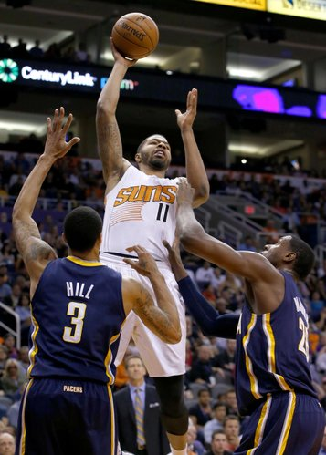 Phoenix Suns' Markieff Morris (11) gets off a shot and scores over Indiana Pacers' George Hill (3) and Ian Mahinmi, right, during the second half of an NBA basketball game Wednesday, Jan. 22, 2014, in Phoenix. The Suns defeated the Pacers 124-100. (AP Photo/Ross D. Franklin)