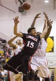 Lawrence High junior Anthony Bonner (15) fights for a rebound against Highland Park's Daniel Kingcannon, right, and Shaffee Carr, left, during the Topeka Invitational championship game, Saturday at Topeka High. The Lions came away with a one point victory, 48-47, taking home the championship.
