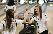 Free State sophomore Gentry Jordan, right, high-fives with classmate Jamie Souders after Jordan rolled a strike during the Free State quadrangular on Tuesday, Jan. 28, 2014, at Royal Crest Lanes.