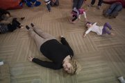 Sarah Niileksela, lays on the floor with Violet Russell, a student at Jump 4 Joy 1035 E 23rd St.