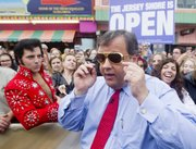 "New Jersey Gov. Chris Christie, right, wears a pair of Elvis glasses he received from Elvis impersonator Craig Newell, left, as Christie mingled with a crowd in May on the Seaside Heights Boardwalk during an appearance on the ""Today"" show. Andrew Mills of the Star-Ledger (NJ) submitted the photograph in the New Jersey Press Association photo contest for 2013 that was judged recently by the photo staff of the Lawrence Journal-World."
