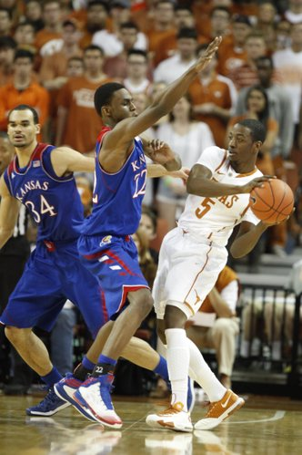 Kansas guard Andrew Wiggins tries to defend a pass from Texas guard Damarcus Croaker during the second half on Saturday, Feb. 1, 2014 at Erwin Center in Austin, Texas. At left is Kansas forward Perry Ellis.
