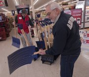 Westlake Hardware Manager Paul Groundwater stocks snow shovels as Lawrence resident Bob Hammersmith chooses one on Monday in anticipation of a winter storm.