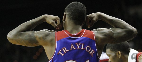 Kansas forward Jamari Traylor flexes his arms from the bench to celebrate a score late in KU's win over the Baylor Bears, Tuesday, Feb. 4, 2014 at Ferrell Center in Waco, Texas.