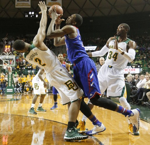 Kansas center Joel Embiid, right, draws a foul charge as he drives into Baylor player Rico Gathers during the first half on Tuesday, Feb. 4, 2014 at Ferrell Center in Waco, Texas.