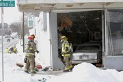 Lawrence-Douglas County Fire Medical crews work the scene of an accident off West Sixth Street in which a driver hit a snowbank and careened through the double doors of Big G's Antiques at the corner of Sixth and Indiana streets. Police responded about 12:40 p.m. Thursday to the accident.