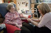 Lucy Seaver, left, gets her blood pressure read by Julie Baldwin, a registered nurse with the Douglas County Visiting Nurses Association, last week at Seaver's Lawrence apartment. The VNA will celebrate its 45th anniversary with an open house Wednesday.