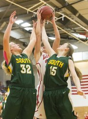 Lawrence High senior Kionna Coleman, center, fight off Shawnee Mission South juniors Ashlie Fischer (32) and Sam Kilzer (15)  to grab a rebound during their game Friday evening at LHS.