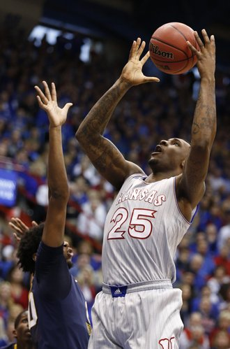 Kansas forward Tarik Black gains control of the ball before a shot over West Virginia forward Brandon Watkins during the first half on Saturday, Feb. 8, 2014 at Allen Fieldhouse.