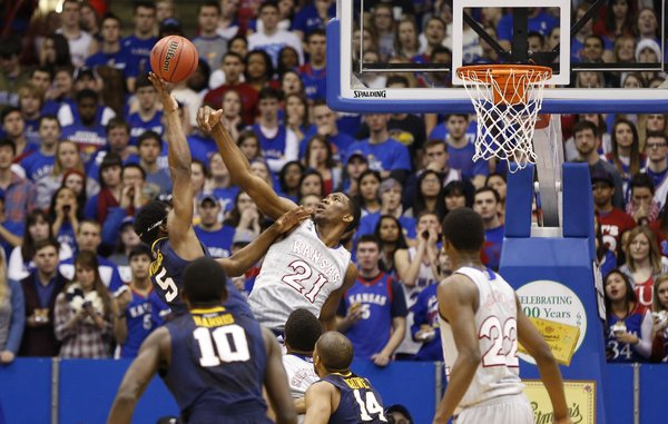 Kansas center Joel Embiid swats away a shot from West Virginia forward Devin Williams during the second half on Saturday, Feb. 8, 2014 at Allen Fieldhouse.