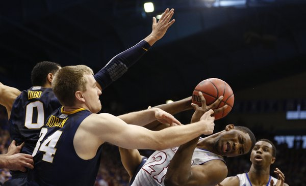 Kansas center Joel Embiid is fouled as he pulls away a rebound from West Virginia forward Kevin Noreen during the second half on Saturday, Feb. 8, 2014 at Allen Fieldhouse.