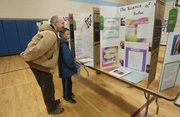 Carl Isenburg and his son Ender 9, a 4th grader at Eudora Elementary School look over some of the Douglas County Science Fair projects at West Middle School on Saturday Feb. 8.