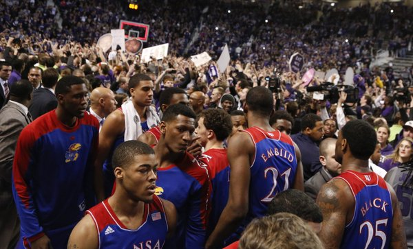 Kansas guard Frank Mason, front, and his teammates look for an exit from the court as the Kansas State student section celebrate following the Jayhawks' 85-82 overtime loss to Kansas State on Monday, Feb. 10, 2014 at Bramlage Coliseum.
