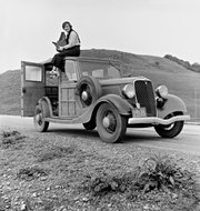 Pictured in 1936, Dorothea Lange is photographed atop a 1933 Ford Model C with her Graflex 5x7 Series D camera. Lange was a New Deal Resettlement Administration and FSA-OWI photographer.
