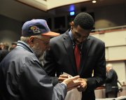 "Justin Wesley — the Kansas University basketball player who played Wilt Chamberlain in the movie ""Jayhawkers"" — signs an autograph for a fan at the movie's premiere Friday at Lied Center. Story on page 3B."