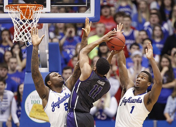 Kansas defenders Tarik Black, left, and Wayne Selden try to smother a shot by TCU forward Brandon Parrish during the second half on Saturday, Feb. 15, 2014 at Allen Fieldhouse.
