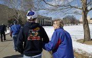 Kansas basketball snowbird Rosalie Gerstner, Ness City, walks arm-in-arm with her grandson Brian Gerstner, Baldwin City, as the two make their way to Allen Fieldhouse prior to tipoff of the Jayhawks' game against the Horned Frogs of TCU on Saturday, Feb. 15, 2014. For years, Gerstner would make the 300-mile trip from Ness City for the home games, but now retired, has decided to rent an apartment in Lawrence during basketball season.